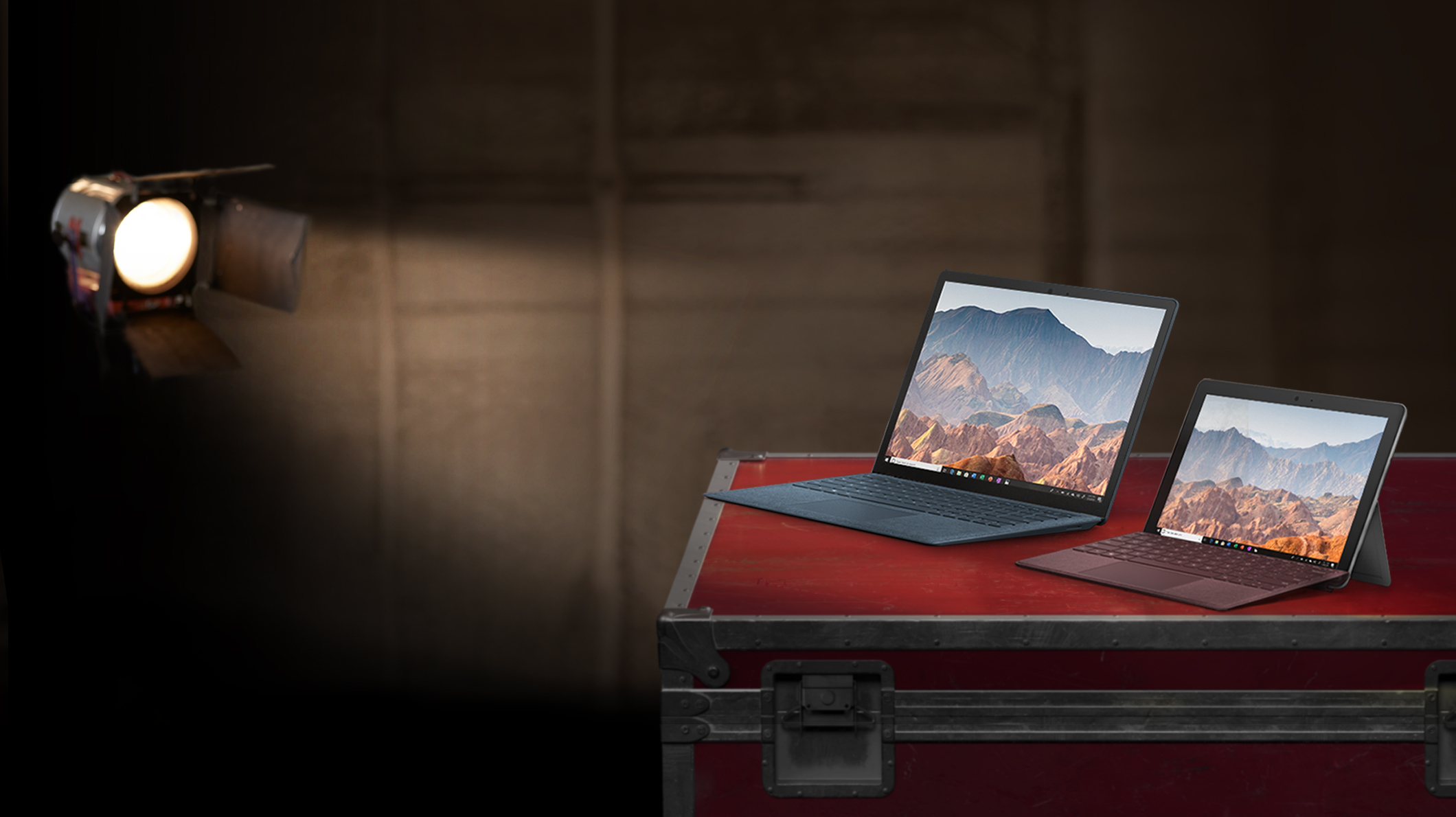 A Surface Laptop 2 and Surface Go under a spotlight on a film set.