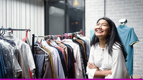 Female business owner smiling next to a rack of clothes.