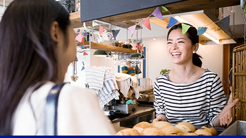 A cafe owner interacting with a female customer at the counter