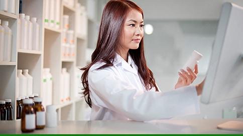 Pharmacist checking medicine prescription label against a computer