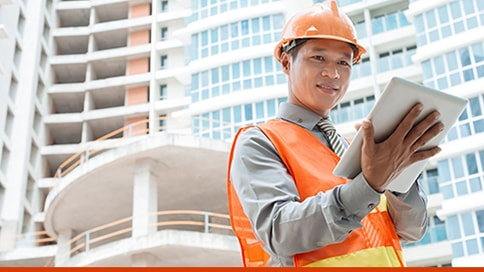 Business owner in safety helmet looking at a tablet under a multi-storey building.