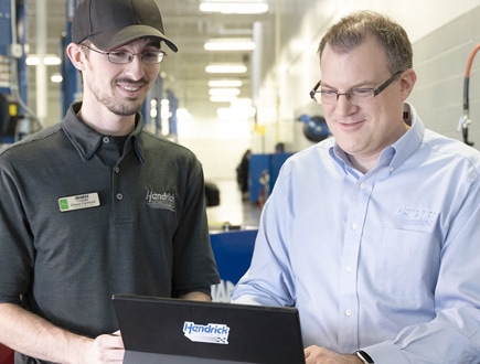 Photograph of a Hendrick mechanic and a manager in an auto shop