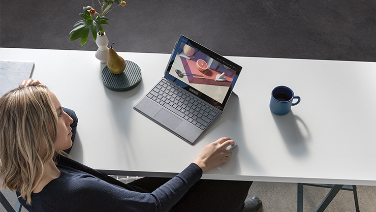 Woman reviewing creative image of fruit on Surface Pro using Arc Mouse