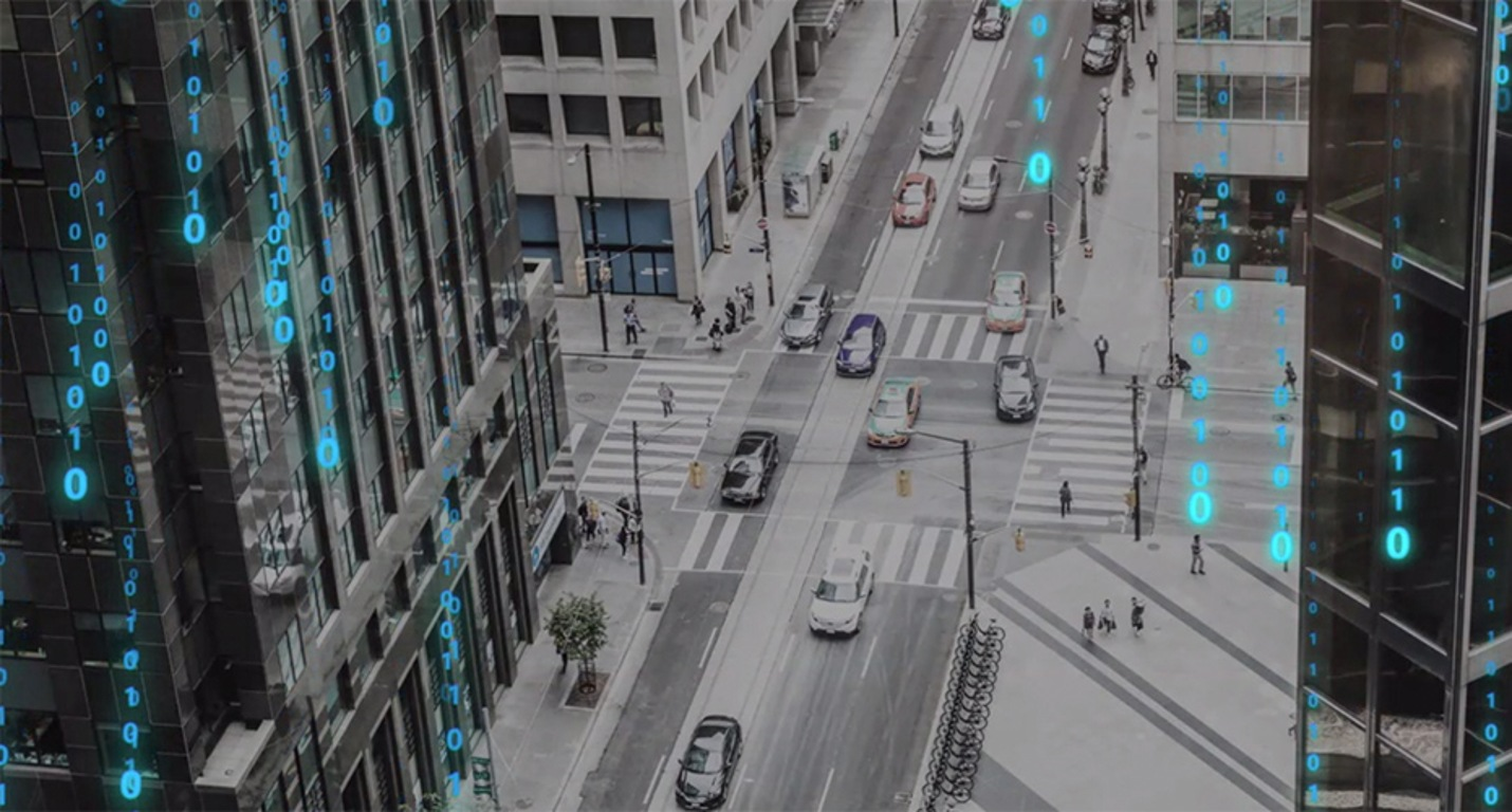 Stylized, filtered photograph of a city street intersection with cars and pedestrians between tall buildings from a high vantage point. Bright blue binary code runs in vertical lines down the photograph.