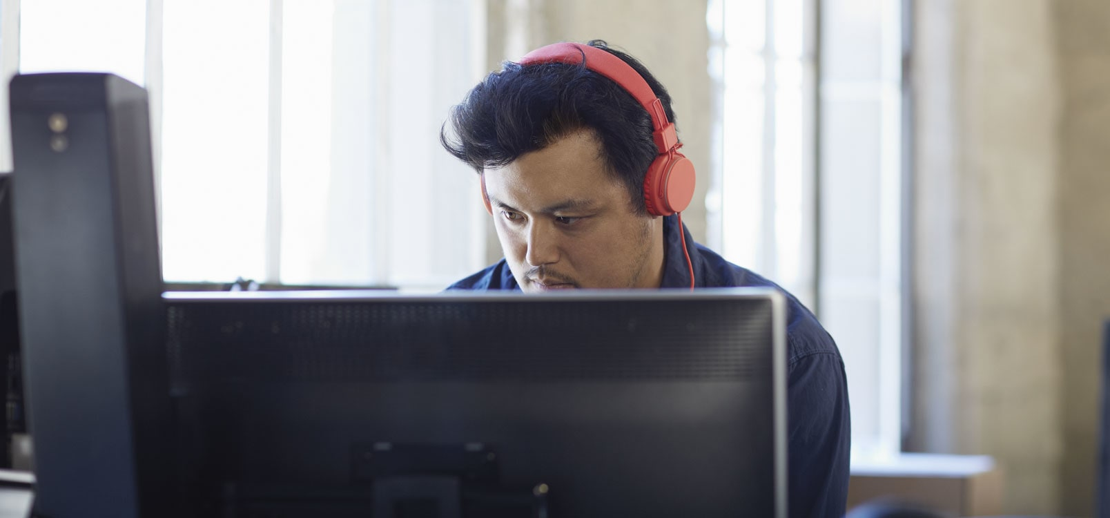 A man wearing headphones working at a desktop PC, using Office 365 to simplify IT.