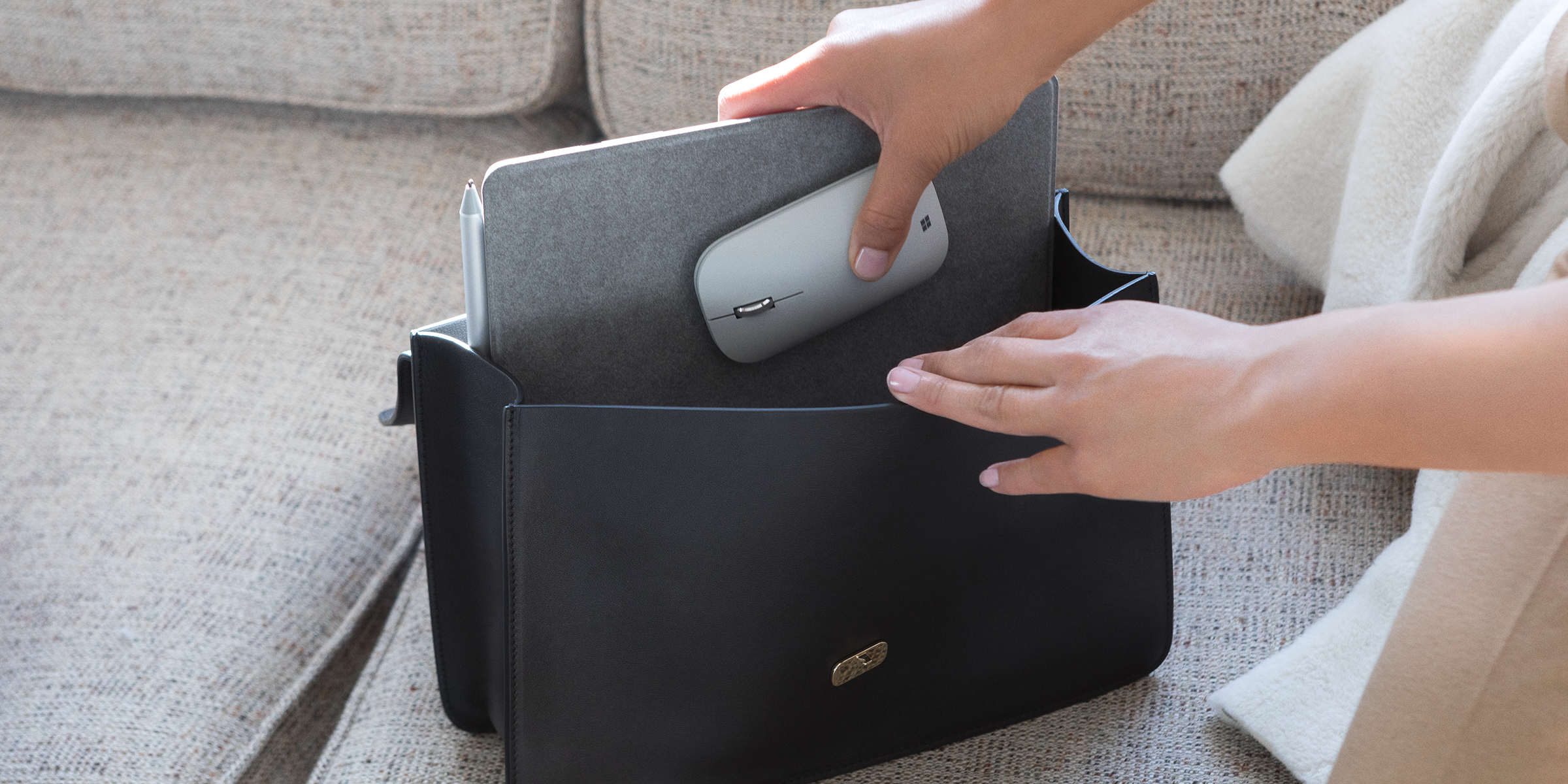 Kobieta wkłada Surface Lingo i Surface Mobile Mouse do torebki