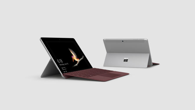 Two Surface Go devices with kickstand down on a flat surface