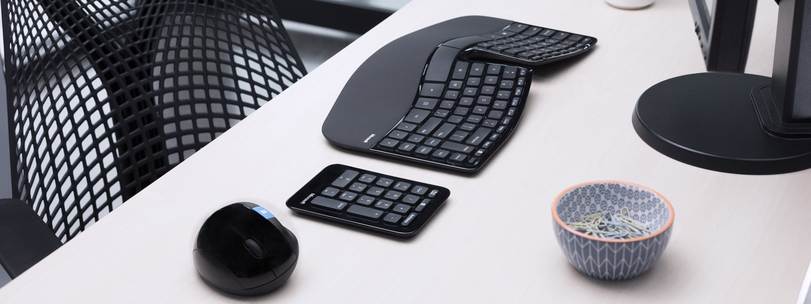 A keyboard and computer mouse sit on a desk.
