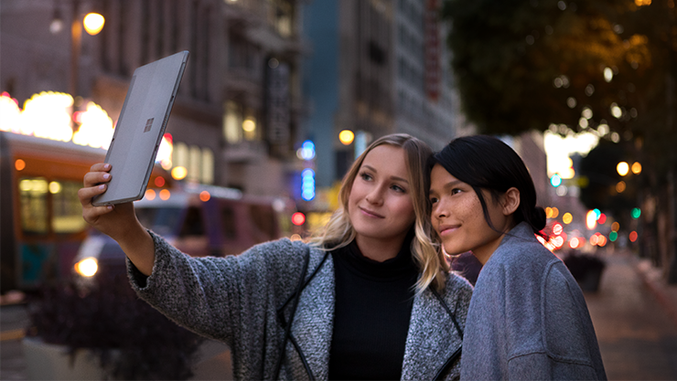 Two women use the Surface Go to take a picture together with the built-in front-facing camera