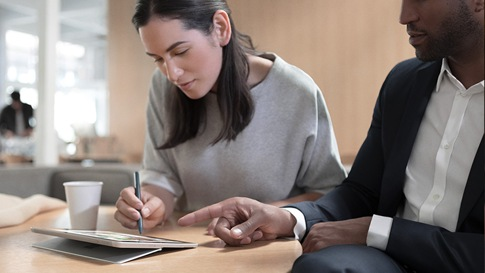 Dos personas trabajan en una Surface Go en un café.