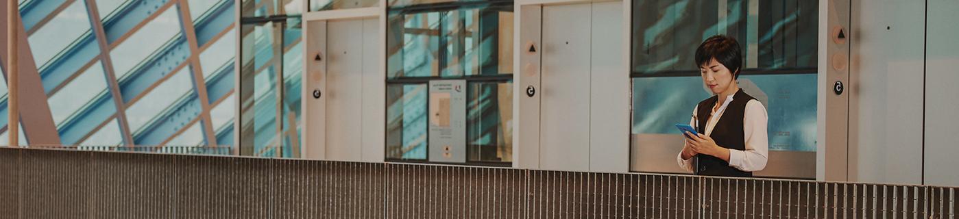 Femme qui regarde un téléphone devant des ascenseurs