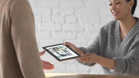 A woman hands a Surface Go to another person