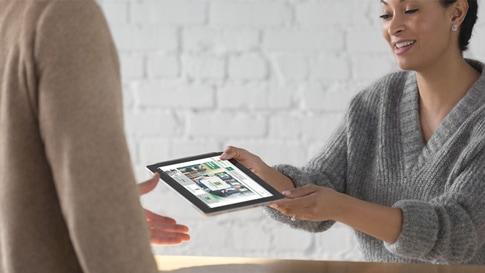Una mujer le da una Surface Go a otra persona