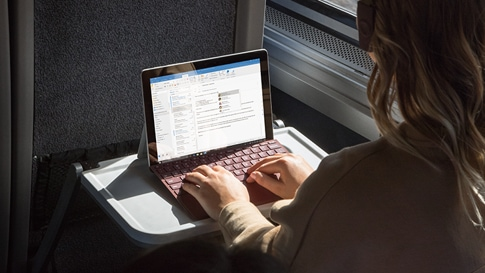 A woman works on Surface Go with Surface Go Type Cover on a train