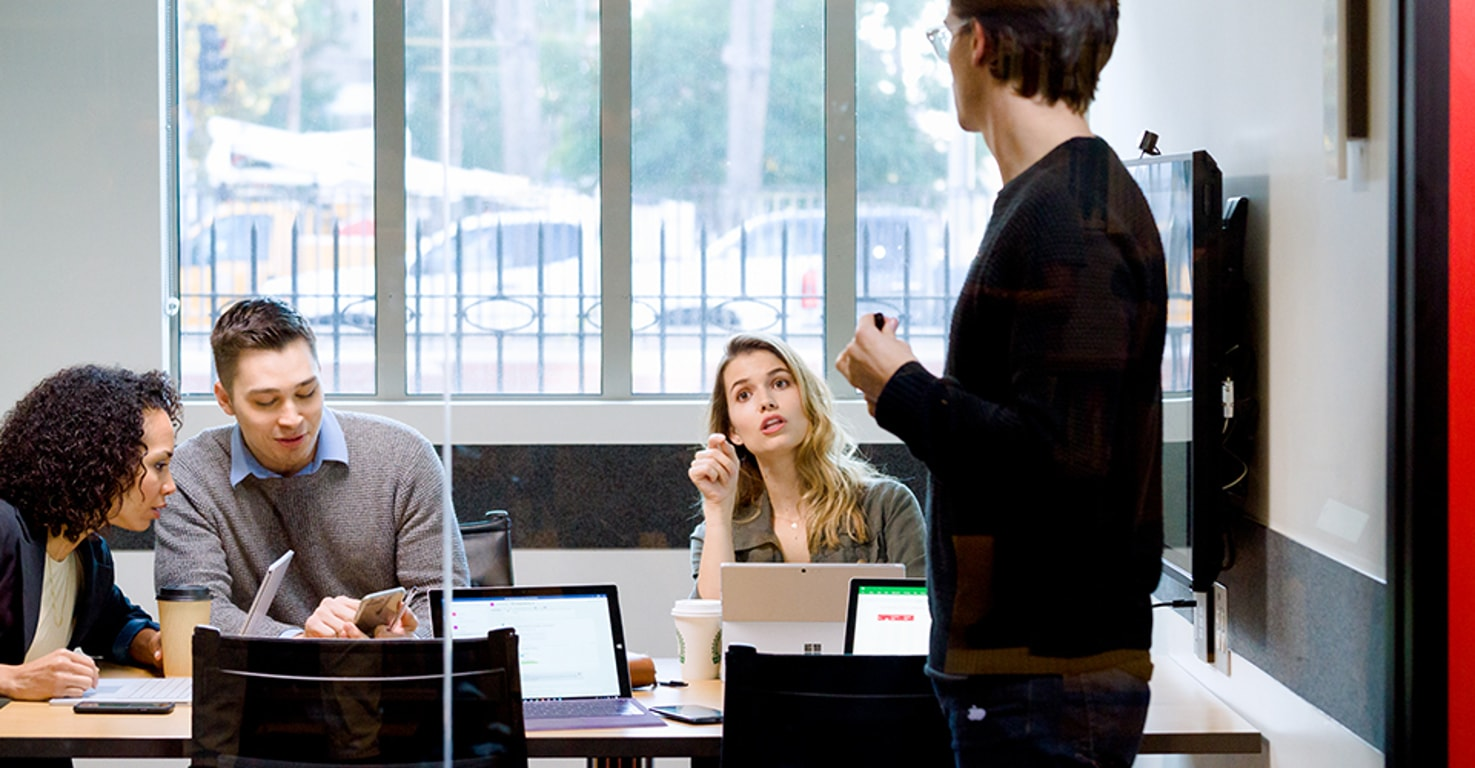 Four people meeting in a conference room with devices open