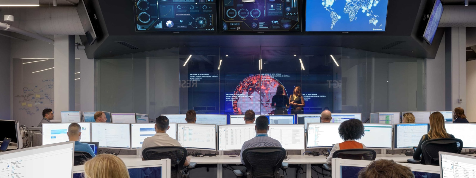 View from inside the Microsoft Cyber Defense Operations Center. People sit at shared desks looking at large desktop monitors. Multiple display monitors are positioned above them at the center of the room, showing various charts and maps.