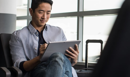 A man writing something down on a tablet.