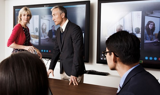 Two business people giving a presentation in front of two Surface Hub screens.
