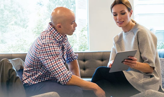 Two people in an office looking at a device