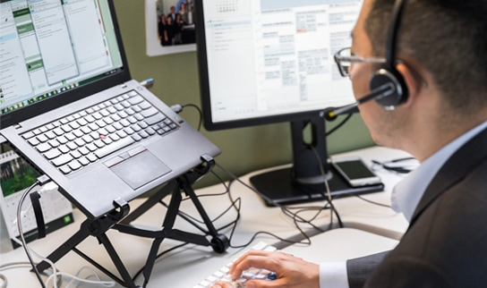Man with a headset working at a laptop workstation.