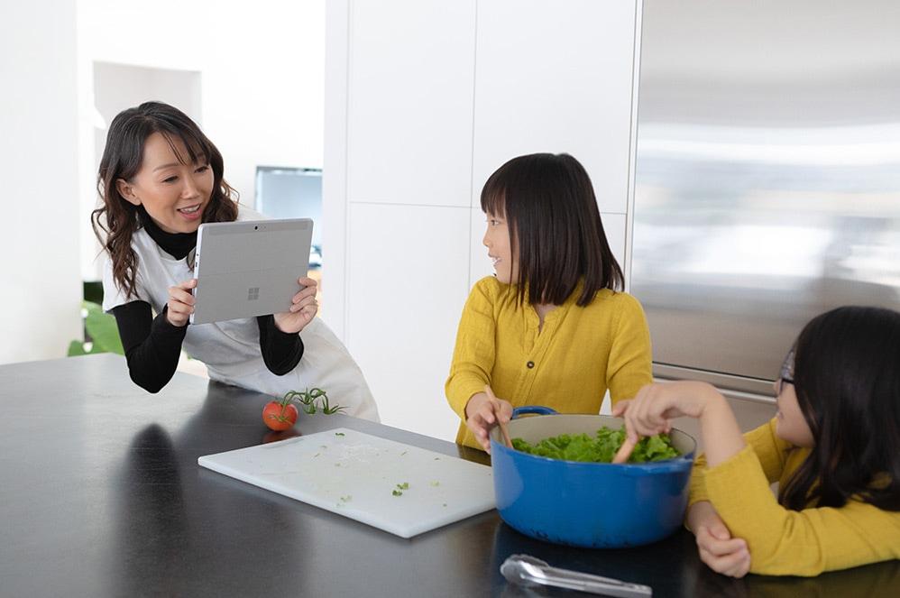 En kvinde tager et billede af sine børn med Surface Go