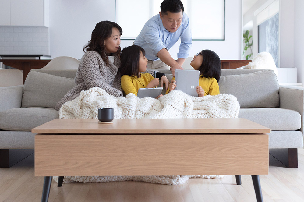 Family sits on a couch with two children each holding a Surface Go