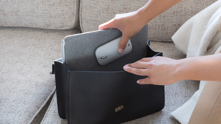 Una mujer pone Surface Lingo y Surface Mobile Mouse en su bolso