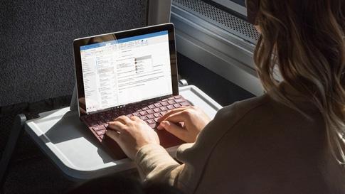 En kvinde arbejder på Surface Lingo med Surface Go Signature Type Cover, mens hun sidder i toget