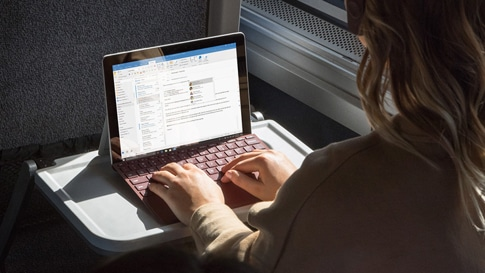 電車で Surface Go Signature Type Cover を付けた Surface Lingo で作業する女性