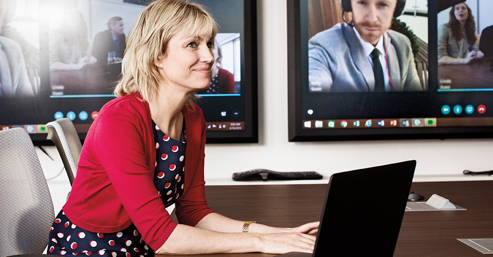 A smiling woman sitting in a conference room with her laptop.