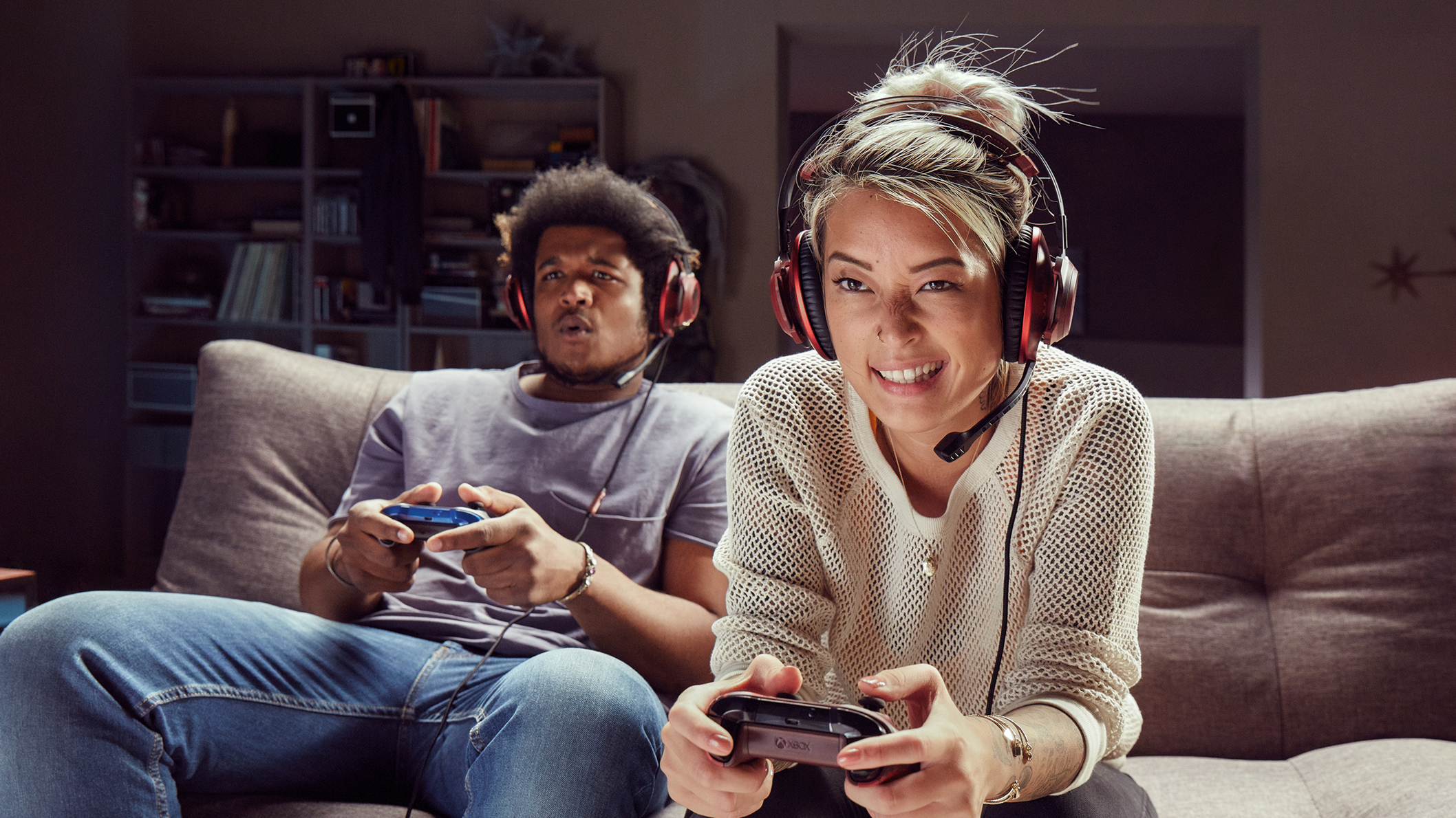 Two people playing with Xbox on a sofa