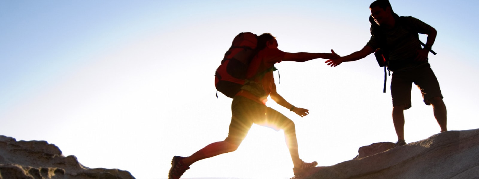 A backpacker in a craggy landscape reaches out to catch the hand of his leaping partner.