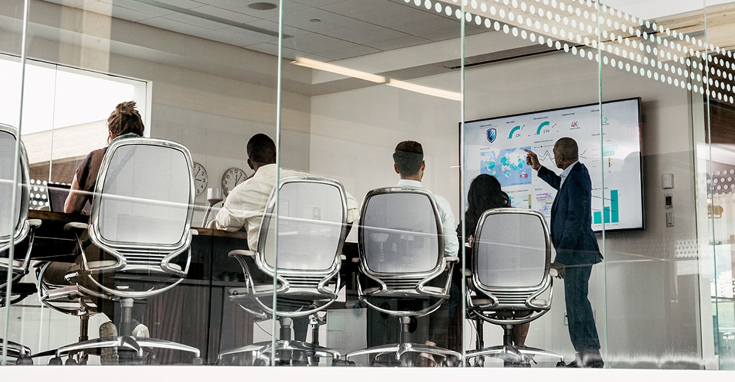 A meeting in a conference room with a presenter pointing at a large monitor displaying data visualizations
