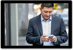 Image of a man standing outside, looking at a mobile phone in his hand