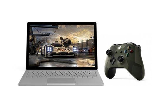 Controlador Xbox con un diseño de camuflaje moderno de color verde oscuro junto a un Surface Book