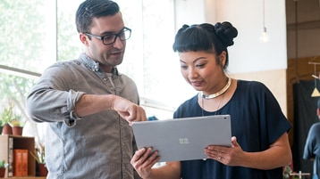 Two people look at a Surface Pro