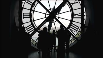 مجموعة من الأشخاص يقفون في الحيز الموجود خلف وجه ساعة عملاقة.