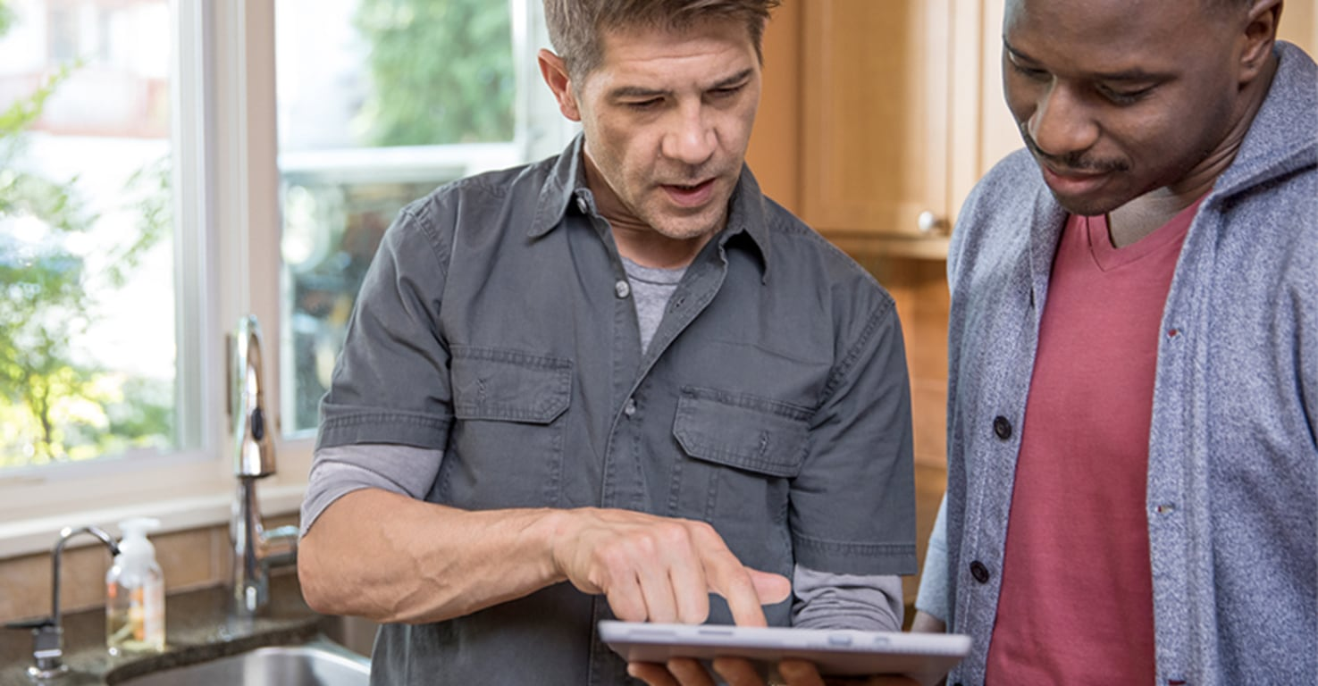 A plumber and client using Office 365 on a tablet device