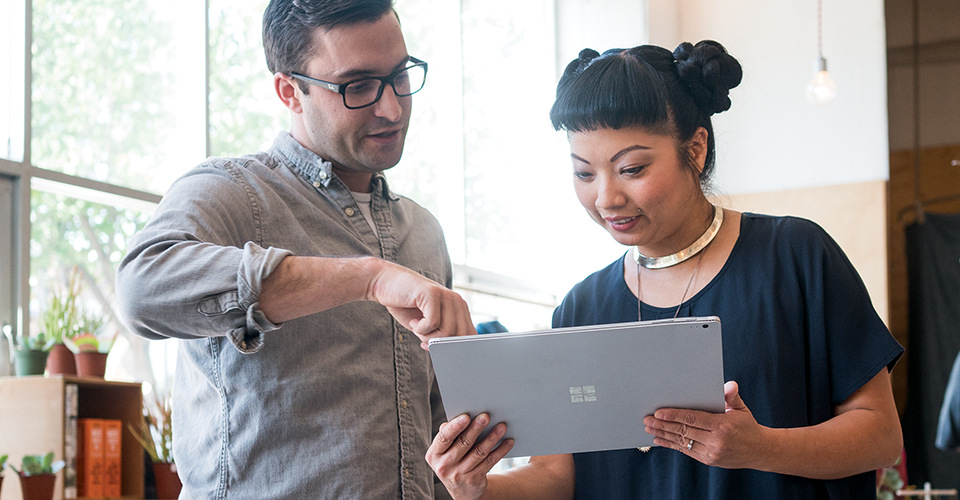 Two coworkers collaborating on a Surface tablet