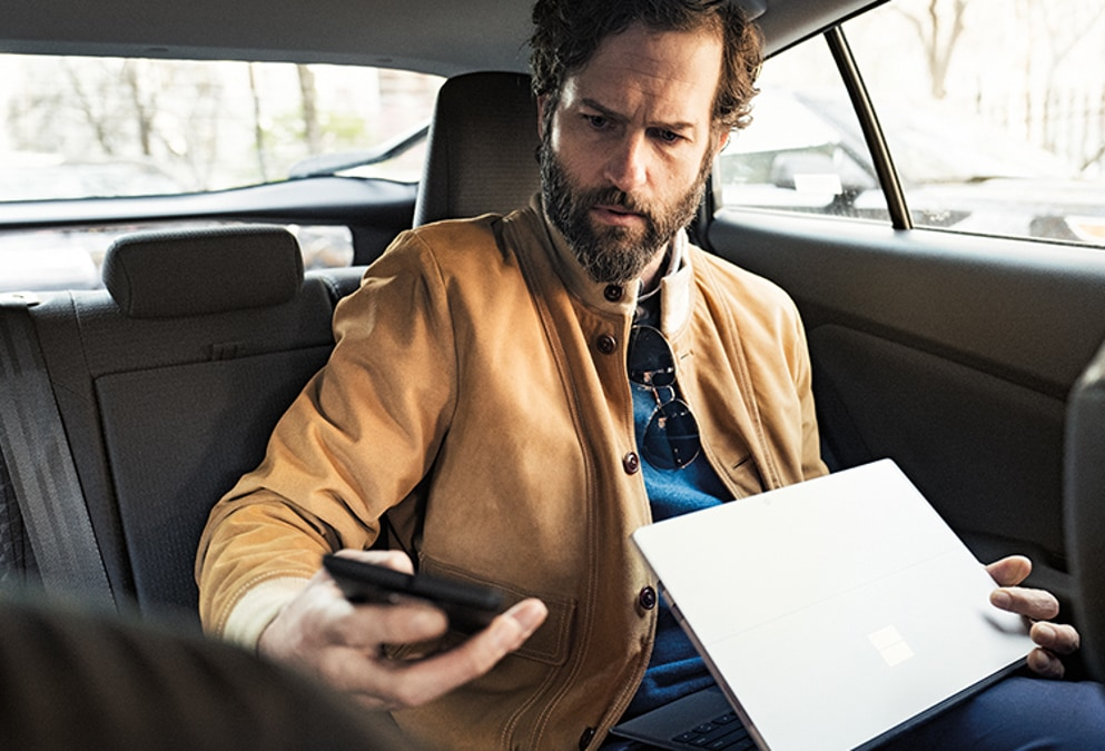 A man using a smartphone and laptop while riding in a car