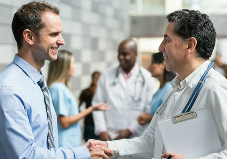 doctors shaking hands with businessman