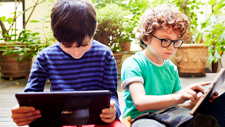 Two young boys use laptops