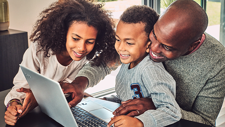 A father and two young children look at a laptop together