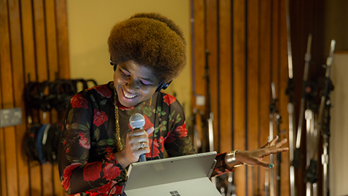 Singer/songwriter SassyBlack in studio holding microphone with Surface device