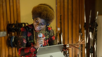 Singer/songwriter SassyBlack in a studio with a Surface device, holding a microphone