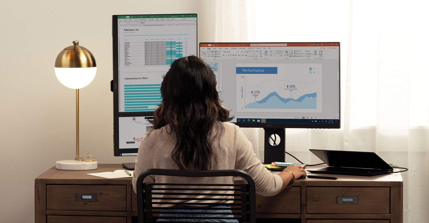 A person sitting at a large desk using Microsoft 365 across two monitors connected to a laptop.