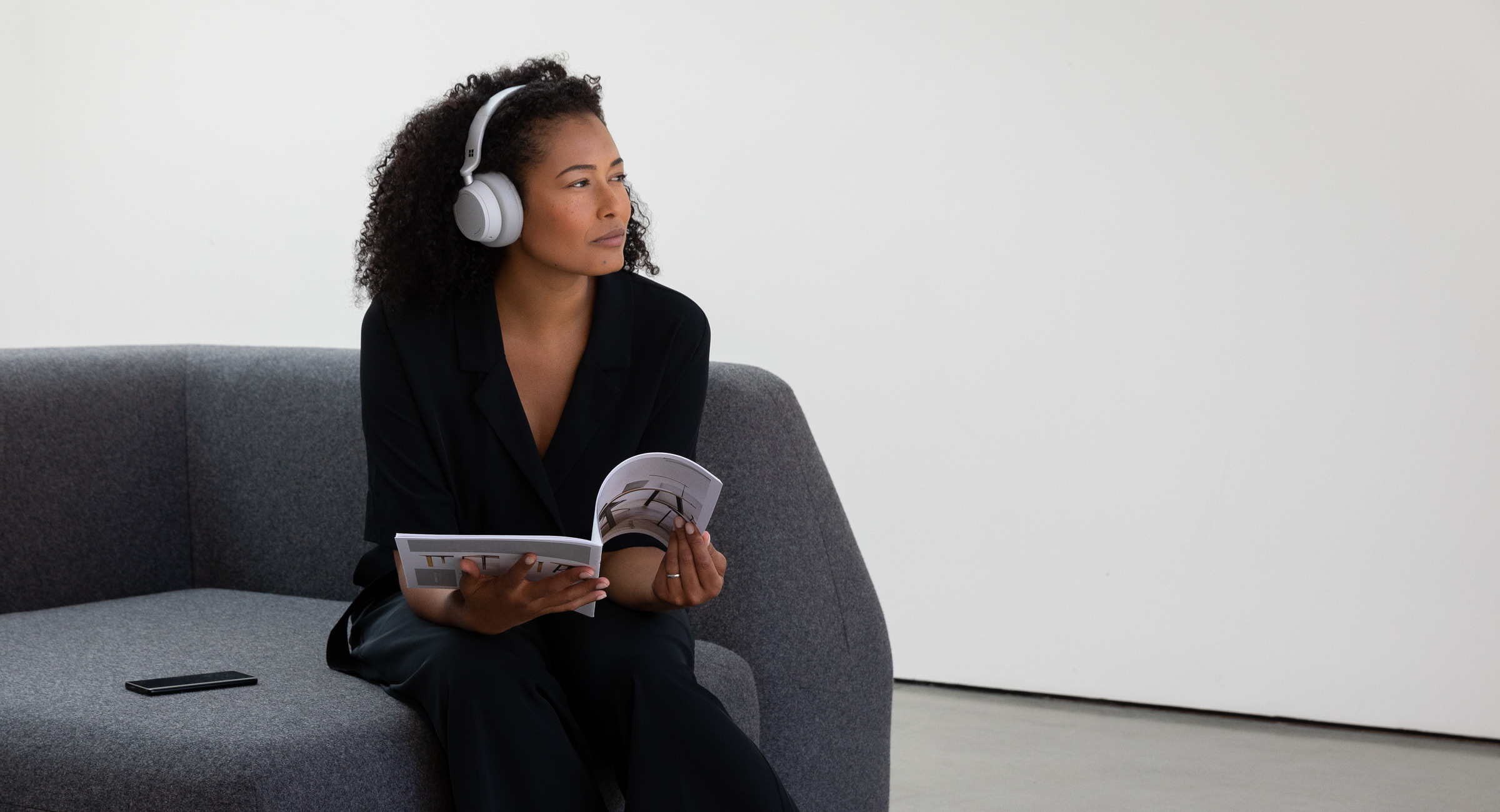 A woman sitting on a couch listening on Surface Headphones