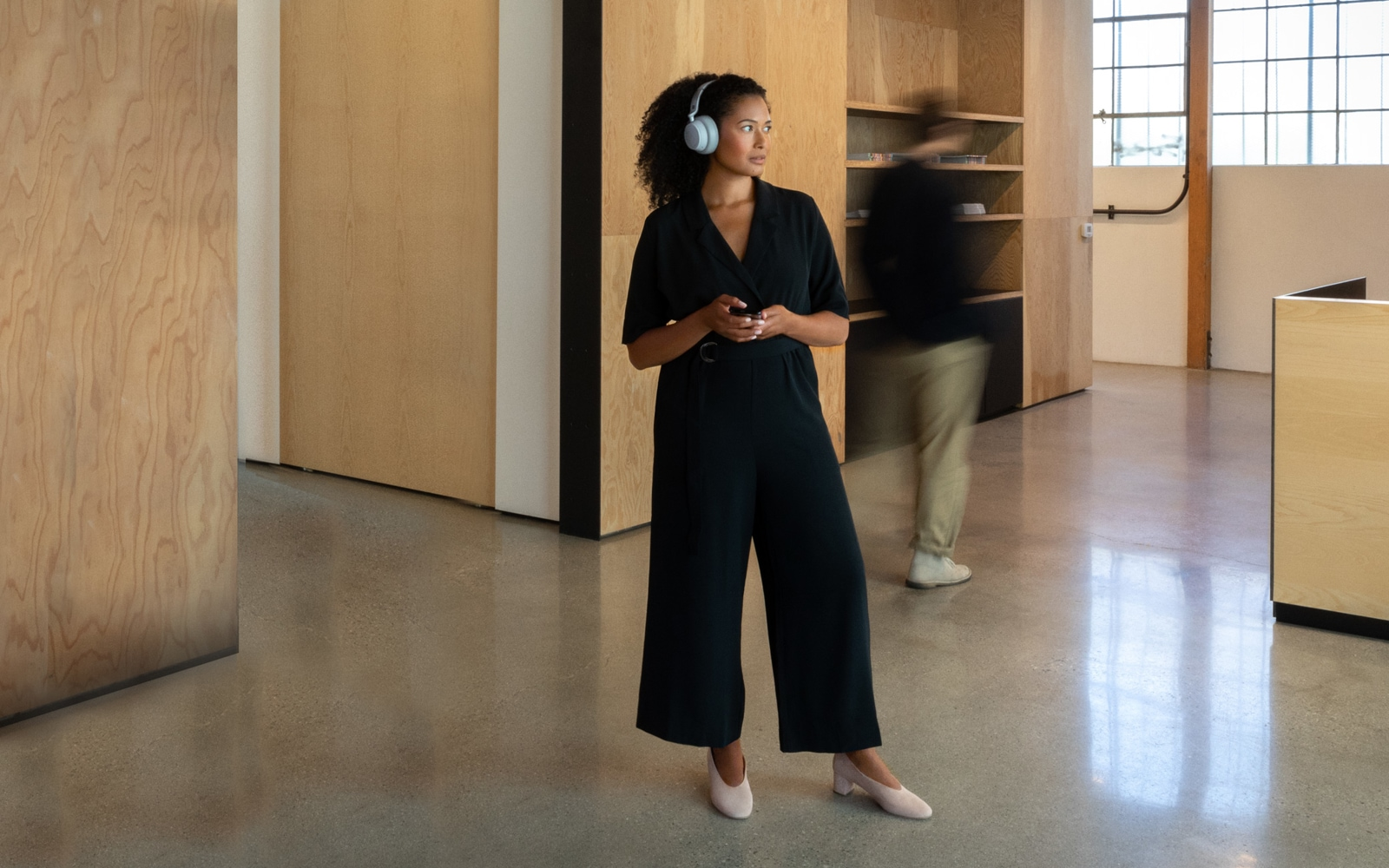 A woman standing with Surface Headphones on her head