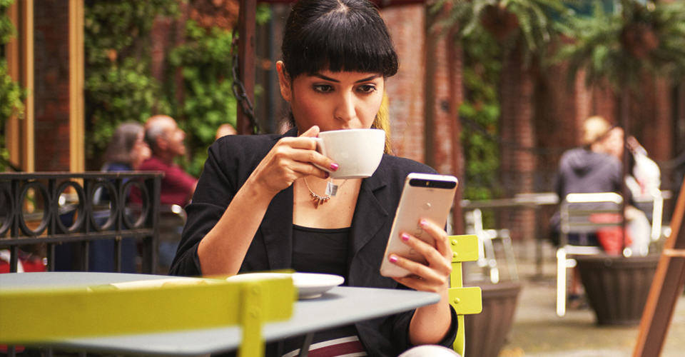 Photo of a woman sipping coffee and looking at her phone