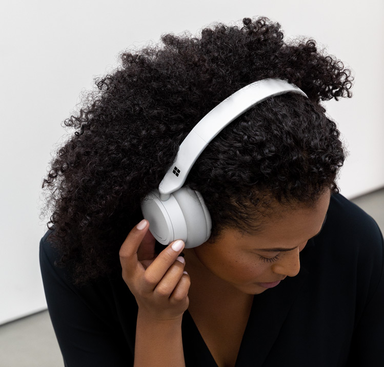 A woman listening and talking with Surface Headphones on her head